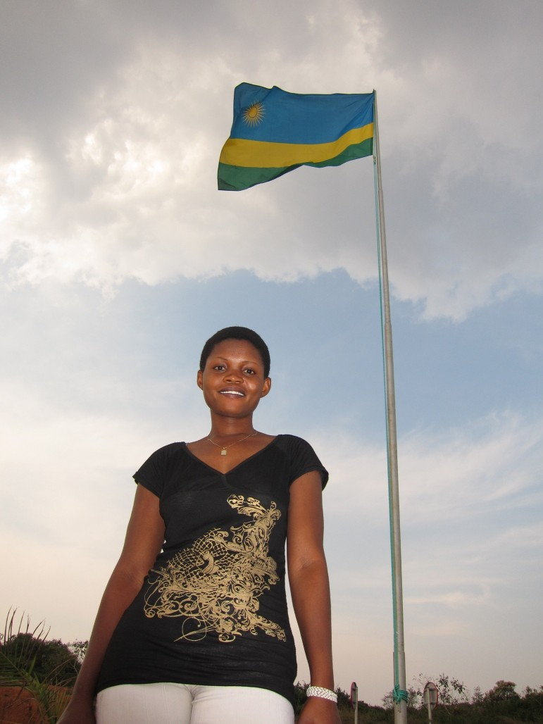 Amina under Rwandan flag at border.